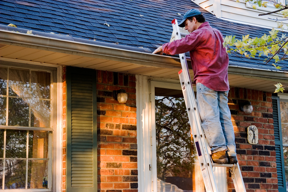 Man Cleaning and doing home repairs on Gutters while atop Ladder